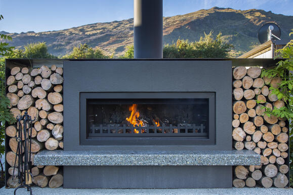 outdoor entertaining area with an outdoor fireplace in Queenstown