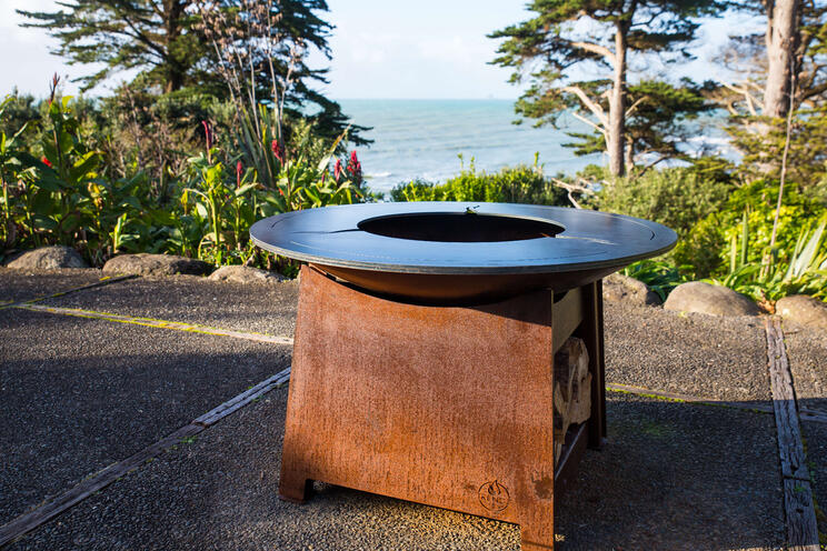 The design of a luxury fire pit includes an area for wood storage