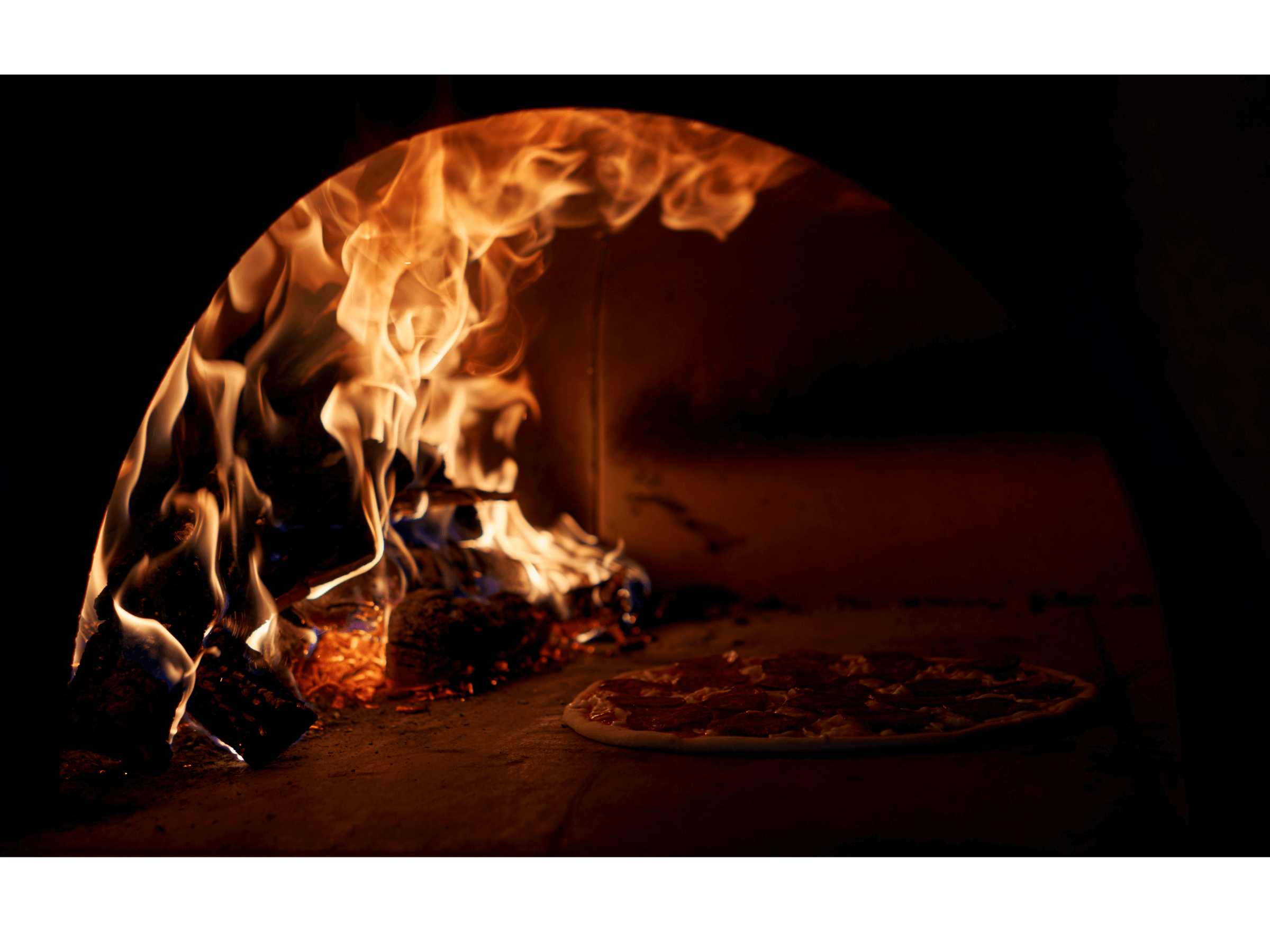 Cooking pizza in a pizza oven